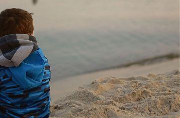 Jongetje met jas en sjaal op het strand op de rug gezien