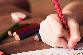 kinderhand schrijft met potlood
